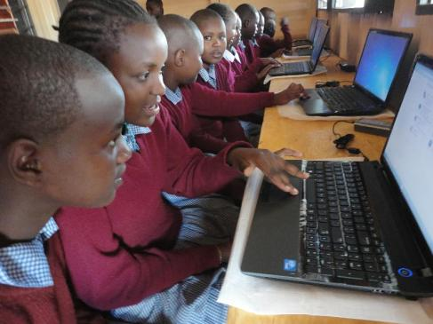 Girls at Ngeya School learning on a computer.